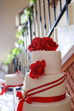 Detail of white wedding cake with red edible flowers Stock Photography