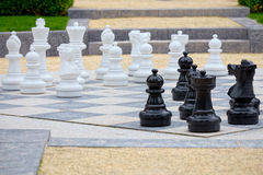 Detail of whites and blacks pieces of an outdoor chess Royalty Free Stock Photography