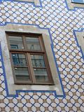 Detail of a window of the façade of a building with the famous azuleioses to Lisbon in Portugal. Window with reflections. Blue and white colors. Wall of the stock photos