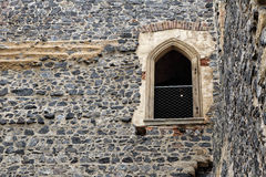 Detail of the window with stony arch frame on the medieval wall. Medieval stronghold door with banisters up the wall Royalty Free Stock Images