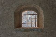 Window with security grating of an ancient castle. Detail of a window with wrought iron grating of an ancient castle Stock Photos