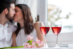 Detail of wine glasses with couple in background. Royalty Free Stock Photo