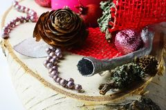Detail of winter christmas decoration with trumpet shaped silver painted piece of wood, red fabric, shiny beads, cones and lichen Stock Image