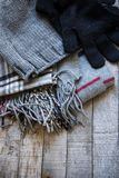 Detail of winter woolen accessory - hat, gloves and scarf on wooden background Royalty Free Stock Photos