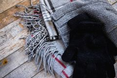 Detail of winter woolen accessory - hat, gloves and scarf on wooden background stock image