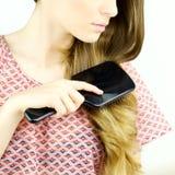 Detail of woman brushing blond long hair Royalty Free Stock Image