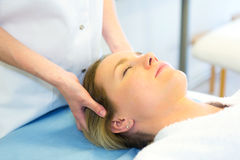 Detail of a woman face receiving a relaxing facial massage Stock Photos