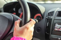 Detail on woman hand on leather car steering wheel. While driving Stock Photography