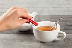 Detail on woman hand pouring sugar from small packet into cup of. Hot tea stock images
