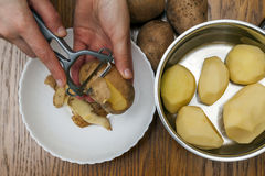 Detail of woman hands peeling fresh yellow potato with kitchen p Royalty Free Stock Photography