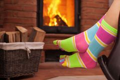 Detail of woman relaxing in front of fireplace Stock Image