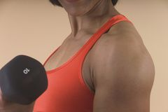 Detail of woman lifting weights. Arm and shoulder of a woman lifting weight Royalty Free Stock Photos