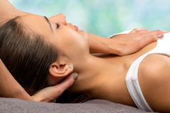 Detail of woman receiving neck therapy. Close up detail of therapist doing osteopathic neck treatment on woman against colorful background Stock Photos