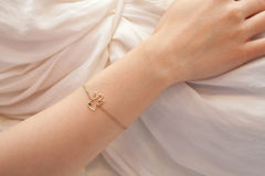 Detail of woman's hand with angel bracelet Royalty Free Stock Photo