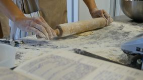 Detail of woman`s hand rolling out a dough with a rolling pin while making homemade pasta. Woman`s hands rolling dough stock photography