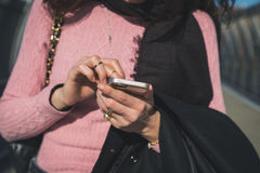 Detail of a woman texting in the city streets Royalty Free Stock Image