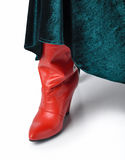 Detail of women's clothing. Fragment of women's clothing. Red leather boots and green velor skirt Royalty Free Stock Photos