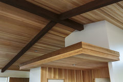 Detail of wood beam ceiling in a modern house entryway. Detail of sloped wood beam ceiling with supports and wooden platform in house entryway Royalty Free Stock Images
