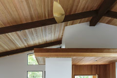 Detail of wood beam ceiling in a modern house entryway. Detail of sloped wood beam ceiling with supports and wooden platform in house entryway. Trees can be seen Royalty Free Stock Image