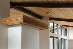 Detail of wood beam ceiling in a modern house. Detail of sloped wood beam ceiling  with modern ceiling fan in a mid-century house. Also seen are windows Stock Images