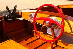 Detail of Wood Speed Boat with Bright Red Steering Wheel at Dock with gears and speedometer royalty free stock image