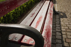 Detail of wooden bench in the city park with cobbles. Closeup shot royalty free stock image