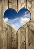 Detail of a wooden door with heart. Blue sky hole in a wooden brown wall background Stock Photos