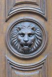Lion head. Detail of a wooden door with lion head decoration Stock Images