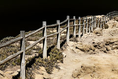 Detail of a wooden fence built on rocky ground - toned image Stock Image