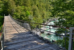 Detail of a wooden foot bridge over a mountain river with blue-green cold water, big stones and freen forest around Stock Photography