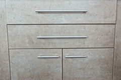 Detail of wooden grey chest of drawers and door in a room Royalty Free Stock Photos