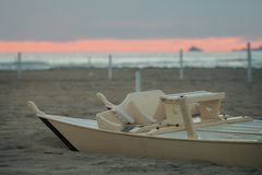 Detail of wooden oar boat  half buried by the sand on the beach Stock Photo