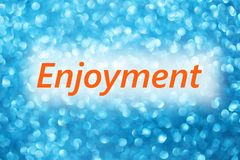 Detail of word Enjoyment on a shiny blurred blue background.  Stock Photo