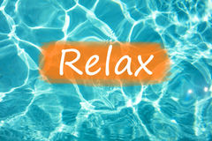 Detail of word & x22;Relax& x22; on swimming pool water and sun reflecting on the surface.  Royalty Free Stock Photos