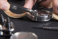 Detail of the work of a watchmaker who replaces a battery. Close up of replacing a watch battery with watchmaker tools stock images