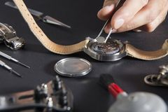 Detail of the work of a watchmaker who replaces a battery. Close up of replacing a watch battery with watchmaker tools stock image