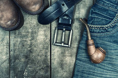 Detail of worn blue jeans and brown shoes on a wooden background Stock Photos