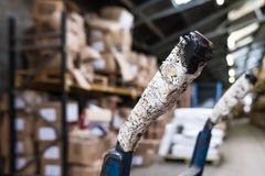 Close-up, shallow focus of a handle of a wheelbarrow, used to move goods in a distribution facility. Stock Photo
