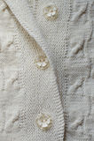 Detail of woven hand made knit sweater or cardigan. Closeup on detail of woven handicraft knit woolen design texture and button. Fabric white background royalty free stock photo