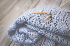 Detail of woven handicraft knit woolen design texture and knitting bamboo needle. Toned retro. Rustic wooden background. Detail of woven handicraft knit woolen stock photography