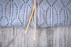 Detail of woven handicraft knit woolen design texture and knitting bamboo needle. Toned retro. Rustic wooden background. Detail of woven handicraft knit woolen royalty free stock images