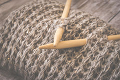 Detail of woven handicraft knit woolen design texture and knitting bamboo needle. Toned retro. Rustic wooden background. Detail of woven handicraft knit woolen stock image