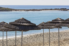 Detail of woven umbrellas above rows on beach in Cyprus. Stock Photography