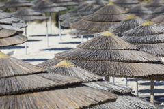 Detail of woven umbrellas above rows of many relaxing beds and l Stock Photos