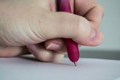 Detail of writing pen. Deatil of hand writing purple pen with hand. Left hand writing Stock Images