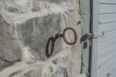 Detail of wrought iron hooks fastened to the stone wall on the r Royalty Free Stock Photo