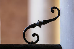 Detail of wrought ironwork. Detail of wrought iron work with an ornamental curlicue in the angle between a wall and rail or balustrade Stock Photo