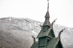 Detail of 1000 year old intricate stave church in Norway with snow-covered mountain in background stock image