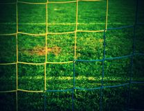 Detail of yellow blue crossed soccer nets, soccer football in goal net with green grass on playground in the background. Royalty Free Stock Photography