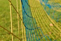 Detail of yellow blue crossed soccer nets, soccer football in goal net with poor grass on playground in background. Royalty Free Stock Photo